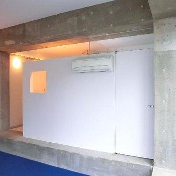 真っ白の壁。小窓から覗くのはキッチンです。