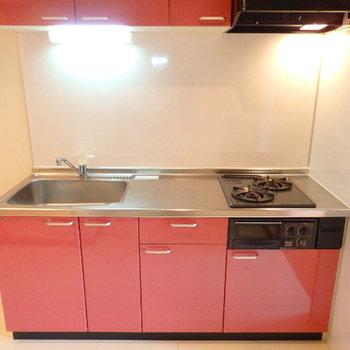 淡いレッドのキッチン。幅広で使いやすそう