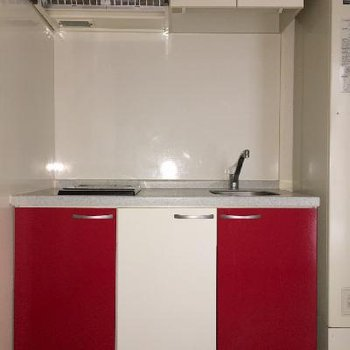 チャームポイントのキッチン。赤と白でお料理が楽しくなりそう。惜しむべくはIH1口。