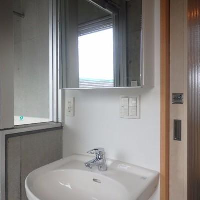 コンパクトな洗面台、鏡の中には収納も。