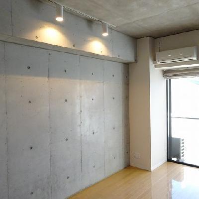 コンクリートの壁際にはライティングレールが※写真は別部屋になります。