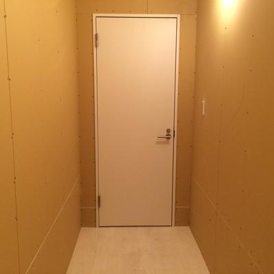 玄関ドアと、ボード仕上げの壁
