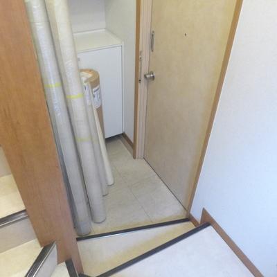 玄関は階段に続いています(写真は物品が置かれています)