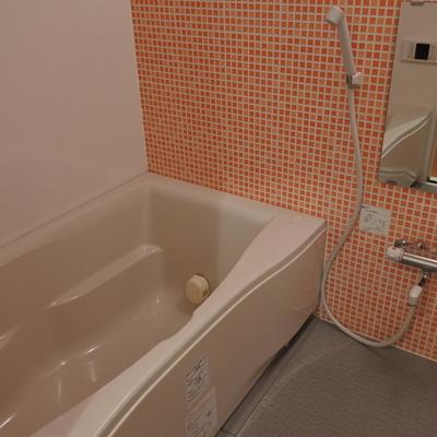 オレンジタイルが目を引くゆったり浴室。