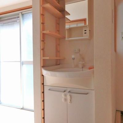 洗面台も木製のシェルフがかわいらしい。