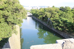 【二条城天守台から本丸南側の内堀を撮影】<p>天守台から内堀の突き当りに桃山門が見える。木々に見えないが、本丸の南東(写真の左側)には二重櫓があった。</p> <p>桃山門は今はなき女院御殿の入り口だった。<br>位置的には女院御殿は桃山門の右側(南側)にあった。</p>