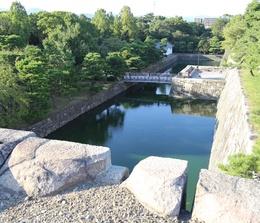 【二条城天守台から本丸西枡形を撮影】<p>二条城天守台から北側の本丸西枡形を撮影。</p> <p>西枡形に木橋の西橋がかかっている。水掘の奥に白い建物があり、これが米蔵で、現存する3つの米蔵の1つ。ちなみに、現存する米蔵はすべて二条城にある。</p>