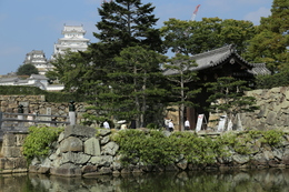 【姫路城大手門】<p>姫路城大手門の高麗門(右)と背後の天守。<br>左手の橋が桜門橋で、2007年に江戸期の木橋をイメージして復元されたとのこと。</p> <p>江戸城や大坂城の大手門は切込み接ぎの石垣だが、姫路城の大手門は意外と巨石は少なく規格化されていなかった。</p>