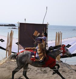 【新井城】2013年「道寸祭り」の笠懸。<br>      的中すると、「コンッ」という板が割れる音がする。<br><br>      弓の長さが目を引く。<br>      実際、騎乗の際や騎乗での所作を見ていると、長弓を扱うのは難しそうだった。モンゴルに代表されるように、騎兵の弓は短弓を中心に進化したが、笠懸の様子を見ているとなるほどと思った。<br><br>      長弓の方が威力はあるだろうが、連射が難しく、精度は各人の技量に委ねられるのではないか。であれば、大量・即座に長弓騎兵を集めるのは難しいはず。