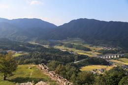 【竹田城】左の曲輪が花屋敷で、右手に播但連絡有料道路にかかるめがね橋が見える。<br>      写真の中央奥が竹田城撮影ポイントの1つ、藤和峠。