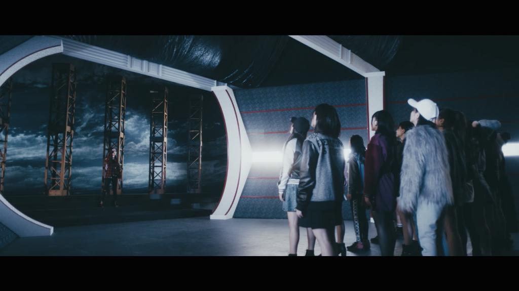 NMB48 16thシングル「僕以外の誰か」の公式MVより。冒頭で、センターの山本彩がメンバーらに向かってマイクを投げるシーンが流れる。