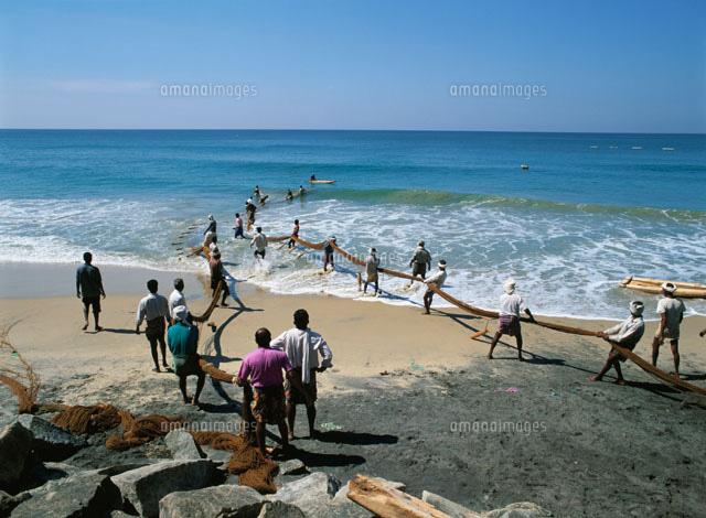 海岸で漁網を引く漁師たち