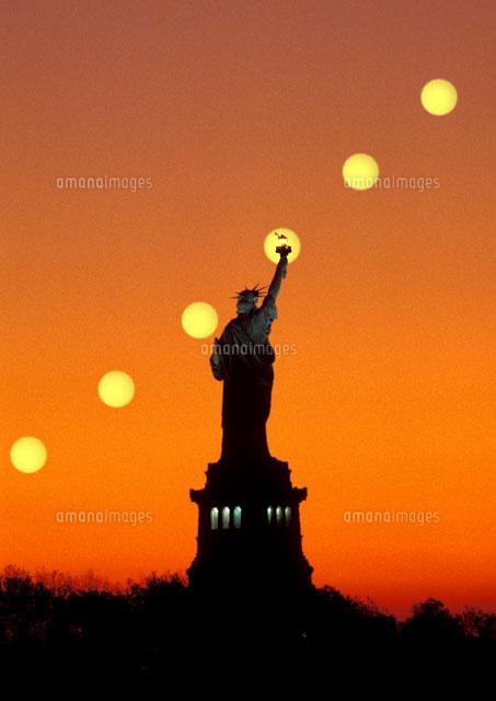自由の女神の背後に昇る朝日