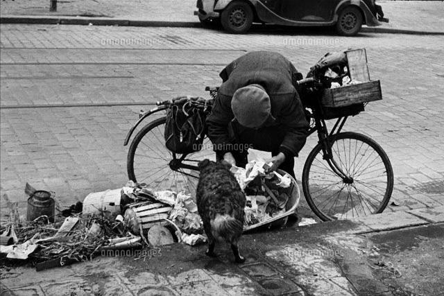 自転車ごしにゴミをあさる男性 ...