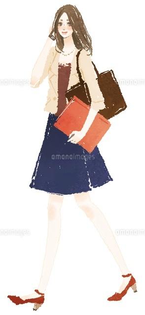 携帯電話で話しながら書類を抱えて歩く女性 (c)Asterisk