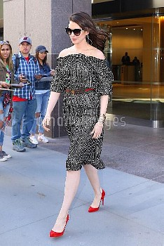 Anne Hathaway wears an off-the-shoulder dress with bright red high heels after a round of interviews