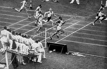 (R-L) USA's Jesse Owens breaks the tape to win gold as teammate Ralph Metcalfe comes home to win sil
