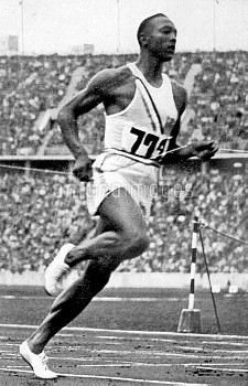 Jesse Owens breaks the tape to win gold