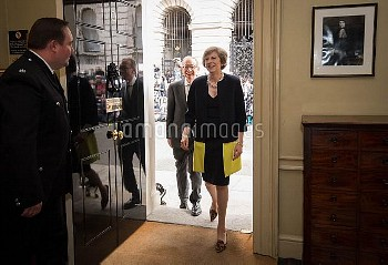 New Prime Minister Theresa May, followed by her husband Philip John, walks into 10 Downing Street, L