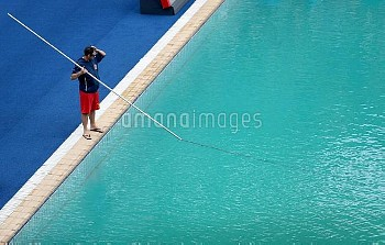 Pool staff clean the diving pool at the Maria Lenk Aquatics Centre on the seventh day of the Rio Oly