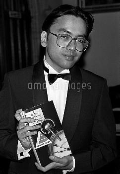 """PA NEWS PHOTO 26/10/89  JAPANESE AUTHOR KAZUO ISHIGURO WITH HIS BOOK """"REMAINS OF THE DAY"""" AT LONDON'"""