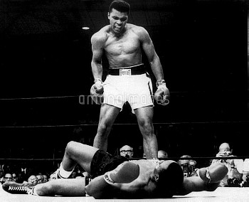 Champion Cassius Clay stands over Sonny Liston and taunts him to get up.  25th May 1965.