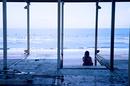 取り壊しの進む海の家の階段に腰掛け海を眺める若い女性