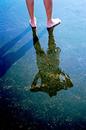 波に濡れた突堤に立つ素足の男性