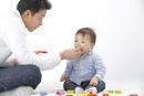 赤ちゃんにお菓子を食べさせるお父さん
