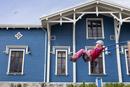 青い家とブランコをする少女
