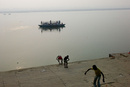 ガンジス川沿いで遊ぶ少年たちと舟で行く人々