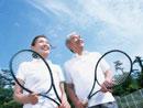 テニスラケットを持つ中高年夫婦