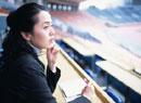 ほおづえをついてメモを取る40代の日本人女性