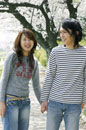 桜並木を歩くカップル