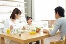 テーブルにのった食事を囲み笑顔で食事している家族三人