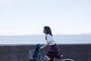 海岸線の道を自転車に乗る笑顔の女子高生