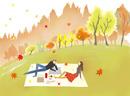秋の公園でピクニック中のカップル