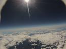 飛行機と同程度の高度からのバルーン空撮 空は黒く近付く 深い紺色の空に浮かぶ太陽