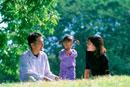 公園に座る家族3人