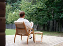 テラスの椅子に座りグラスを持つ男性後姿
