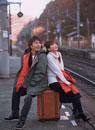 駅のホームで電車を待つカップル