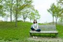 ベンチにあぐらをかいて座る女性