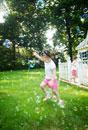庭で走る姉妹とシャボン玉