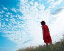 土手に立つ女性と青空