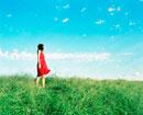 草原に立つ赤いワンピースを着た女性