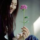バラを見つめて微笑む女性
