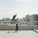 アパートの屋上で傘を構える女性