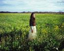 菜の花畑に立つ女性