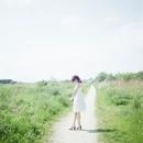 道を歩く白いワンピースの女性