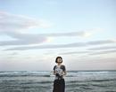 海岸で空を眺める女性